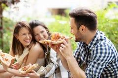 Друзья едят пиццу Стоковая Фотография