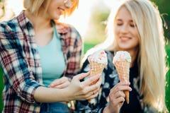Друзья, 2 женщины при мороженое имея потеху Стоковое Изображение