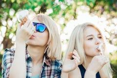 Друзья, 2 женщины при мороженое имея потеху стоковые фото
