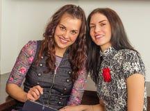 Друзья женщин беседуя дома и используя компьтер-книжку для того чтобы посмотреть новый p Стоковая Фотография RF