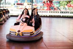 Друзья женщин имея потеху на парке атракционов, автомобиль бампера Стоковое Изображение RF