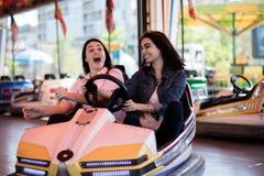 Друзья женщин имея потеху на парке атракционов, автомобиль бампера Стоковая Фотография RF