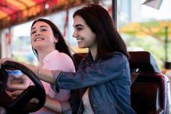 Друзья женщин имея потеху на парке атракционов, автомобиль бампера Стоковые Фотографии RF