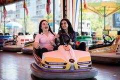 Друзья женщин имея потеху на парке атракционов, управляя автомобилем бампера Стоковое фото RF