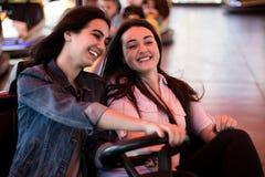 Друзья женщин имея потеху на парке атракционов, управляя автомобилем бампера Стоковые Изображения