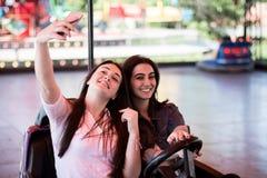 Друзья женщин имея потеху на парке атракционов, управляя автомобилем бампера Стоковые Фото