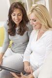 Друзья женщин используя планшет дома Стоковая Фотография