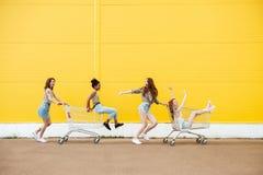 Друзья женщин над желтой стеной Имейте потеху с вагонеткой покупок стоковая фотография