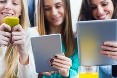 Друзья занимаясь серфингом сеть с smartphones и цифровыми таблетками Стоковая Фотография