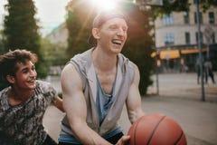 Друзья играя баскетбол и имея потеху Стоковое фото RF