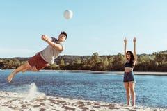 Друзья играя волейбол на песчаном пляже на дневном времени стоковые фотографии rf