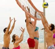 Друзья играя волейбол на пляже Стоковые Фотографии RF
