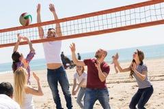 Друзья играя волейбол на пляже Стоковые Изображения