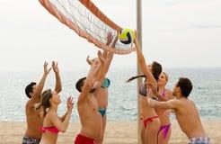 Друзья играя волейбол на пляже Стоковое фото RF