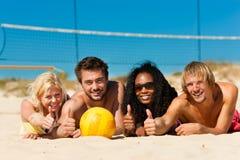 Друзья играя волейбол пляжа Стоковая Фотография