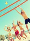 Друзья играя волейбол Стоковая Фотография