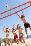 Друзья играя волейбол Стоковые Фото