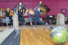 Друзья играя в клубе боулинга стоковое фото rf