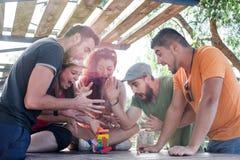 Друзья играя игру блока стоковая фотография rf