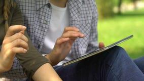 Друзья играя компютерную игру на планшете в парке, часы досуга с мобильным приложением видеоматериал