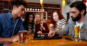 Друзья играя нард пока имеющ пить в баре 4k видеоматериал