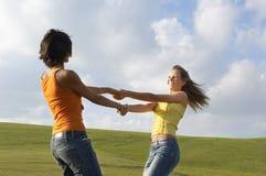 Друзья играя пока держащ руки против облачного неба Стоковые Фотографии RF