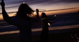 Друзья играя с бенгальскими огнями на пляже 4k видеоматериал