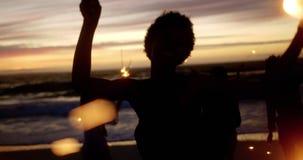 Друзья играя с бенгальскими огнями на пляже 4k акции видеоматериалы
