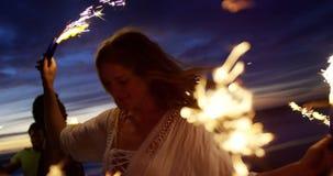 Друзья играя с бенгальскими огнями на пляже 4k сток-видео