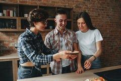 Друзья имеют потеху и едят кухню пиццы дома стоковая фотография rf