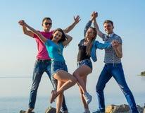 Друзья имеют потеху и танцы вперед на seashore, удерживании ha Стоковая Фотография