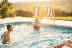 Друзья имея воду брызгая потеху на бассейне стоковая фотография rf
