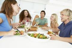 друзья имея домашний обед ослабить стоковые изображения rf