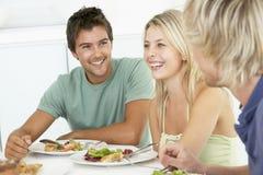 друзья имея домашний обед ослабить Стоковое фото RF