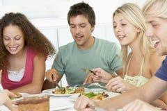 друзья имея домашний обед ослабить Стоковая Фотография RF