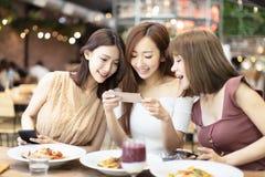 друзья имея обедающий и наблюдая умный телефон в ресторане стоковые фото