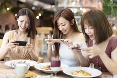 друзья имея обедающий и наблюдая умный телефон в ресторане стоковые изображения
