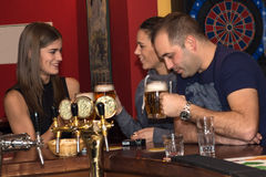 Друзья имея пить в баре стоковое изображение
