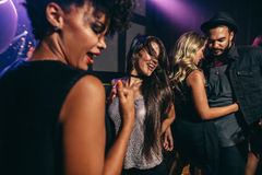 Друзья имея потеху совместно на ночном клубе Стоковая Фотография