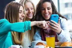 Друзья имея потеху с smartphones Стоковые Изображения