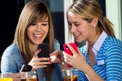 Друзья имея потеху с smartphones Стоковая Фотография
