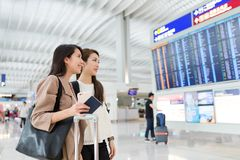 Друзья ища номер рейса в авиапорте Гонконга Стоковое Фото