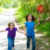 Друзья и девушки сестры бежать в лесе отслеживают счастливое Стоковое фото RF