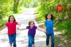 Друзья и девушки сестры бежать в лесе отслеживают счастливое Стоковые Изображения