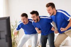 Друзья или футбольные болельщики наблюдая футбол дома Стоковые Изображения