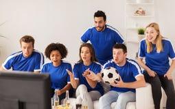 Друзья или футбольные болельщики наблюдая футбол дома Стоковые Изображения RF