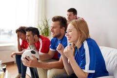 Друзья или футбольные болельщики наблюдая футбол дома Стоковая Фотография RF