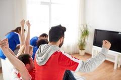 Друзья или футбольные болельщики смотря ТВ дома Стоковая Фотография RF