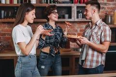 Друзья и пицца 3 молодых жизнерадостных люд есть пиццу, lau Стоковое Изображение RF