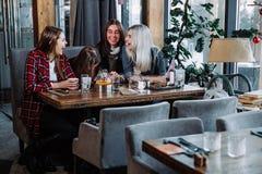 Друзья компании говоря в кафе и имея потеху Стоковая Фотография RF